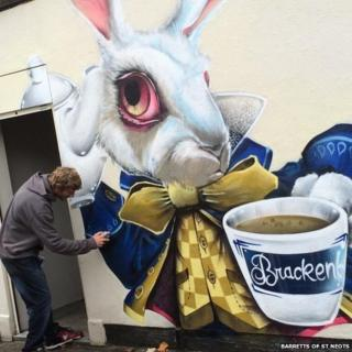 Graffiti artist painting March Hare mural