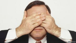 A man in a suit covers his eyes
