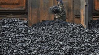 Worker unloading coal from railway in Shenyang, China, file photo from 2010