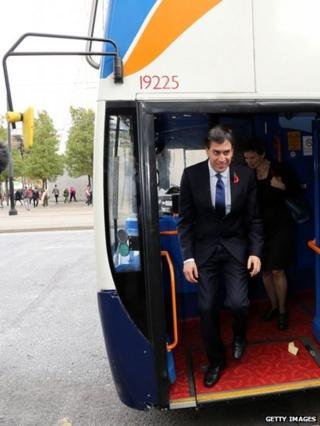 Ed Miliband steps from bus