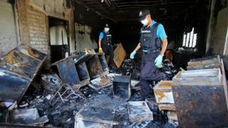 Thai forensic police inspect the burnt remains of the district government bureau after it was allegedly set alight by Muslim militants in Pattani province on October 28, 2014.