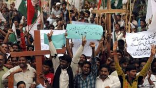 Pakistani Christians shout slogans during a protest against the attack on the homes of members of the Christian community