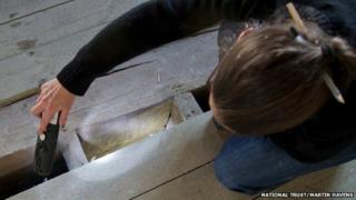 National Trust archaeologist Nathalie Cohen examines witchmarks at Knole