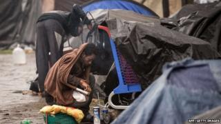 An illegal migrant sits on October 29, 2014 near makeshift tents in the northeastern French port of Calais