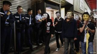 Pro-democracy protesters wearing Guy Fawkes masks walk past policemen on a road occupied by protesters as part of the Occupy Central civil disobedience movement at Mong Kok shopping district 5 November 2014, the day marking Guy Fawkes Night