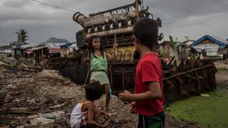 Children play in front of the left over engine of a scrapped tanker that was washed ashore during Typhoon Haiyan last year