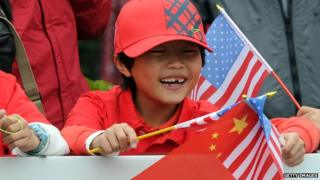Chinese boy waving China and US flags