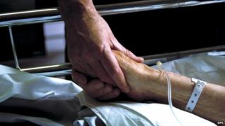 Nurse holding a patient's hand in hospital