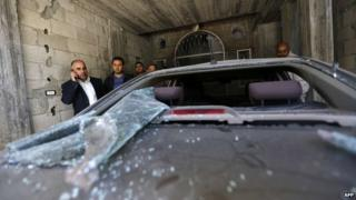 Fayez Abu Eitta (L), a Fatah leader in Gaza, speaks on the phone as he inspects the damage to his car in the parking lot of his home in Beit Lahya, northern Gaza Strip on November 7, 2014.