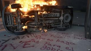 A burning car next to a graffiti outside the State Government headquarters in Chilpancingo, Guerrero State, on November 8, 2014.
