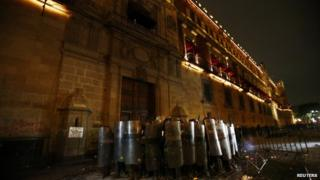 "Policemen block the wooden door of Mexican President Enrique Pena Nieto""s ceremonial palace during a protest 8 Oct 2014"