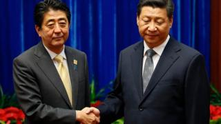 Japan's Prime Minister Shinzo Abe shakes hands with China's President Xi Jinping (R), during their meeting at the Great Hall of the People