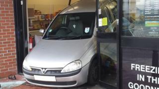 Car reversing through shop window