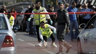 Members of the Israeli Zaka emergency response team work at the scene of a stabbing in Tel Aviv. November 10, 2014