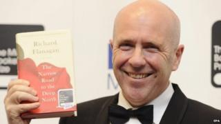 Australian novelist Richard Flanagan holds a copy of his book The Narrow Road to the Deep North
