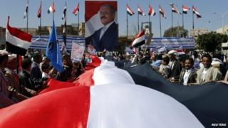 "Supporters of Yemen""s former President Ali Abdullah Saleh hold a huge Yemeni flag next to a poster of Saleh as they rally in his support in Sanaa 7 November 2014"