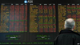 A man looks at the Australian Securities Exchange board in Melbourne - 12 August 2010.