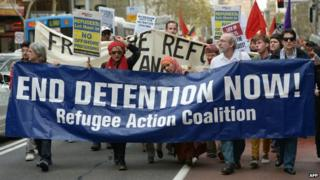 Pro-refugee protesters hold placards as they march with a banner through central Sydney - 28 July 2013