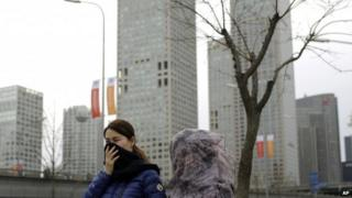 Chinese women cover their face with scarf as they walk past the Central Business District in Beijing, China Tuesday, Nov. 11, 2014