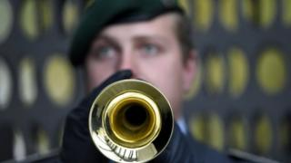 Soldier of the German armed forces plays the trumpet during a welcome ceremony