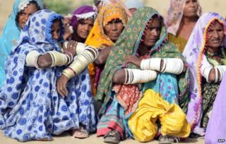 Pakistani villagers wait to receive relief supplies outside a military camp in Mithi, the capital of Tharparkar district, some 300 kilometres from Karachi on 11 March 2014.