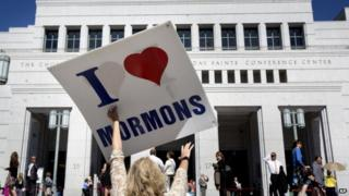 A women holds up a I love Mormon sign in Salt Lake City