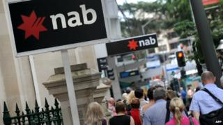 People walk past National Australia Bank signs adorning a building in central Brisbane - 5 December 2011