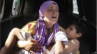 Syrian woman carrying wounded son (file photo)