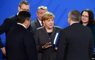 Angela Merkel, surrounded by cabinet ministers, is handed a report by Germany's council of economic advisers (12 Nov)