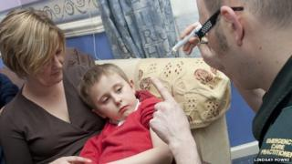 Paramedic treating child at home