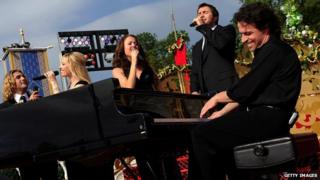 Yanni playing the piano on stage with four vocalists