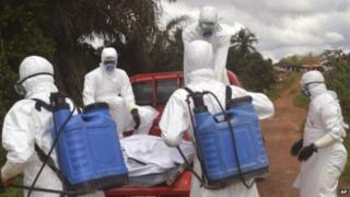 Health workers load the body of a woman suspected of dying from Ebola onto a car in Jene-Wonde, Liberia. Photo: 8 November 2014