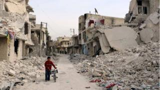 A Syrian boy walks with his bicycle in the devastated Sukari district in the northern city of Aleppo on 13 November 2014