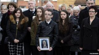 Mourners gathered behind a photograph of IRA murder victim Brendan Megraw at his funeral in west Belfast on Friday