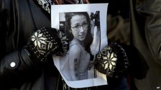 Woman holds a picture of Rehtaeh Parsons in Halifax, Nova Scotia on 11 April 2013