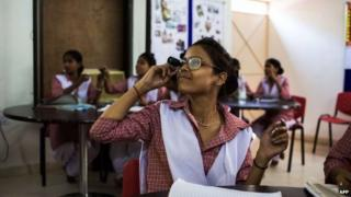 Female student in class in New Delhi looks through eye-glass