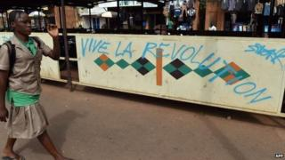 "A schoolgirl walks past graffiti ""Blaise go away"" ""Long live the revolution"" on November 6, 2014 in Ouagadougou"
