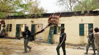 File photo: Police officers walking past the Chibok school where more than 200 schoolgirls were abducted by Boko Haram Islamists, 21 April 2014