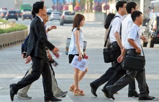 Korean office workers cross a road in Seoul