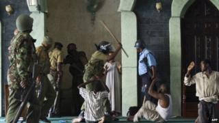 File photo: A police officer hits men as police storm the Masjid Musa Mosque and detain alleged jihadist radicals in the Majengo area of Mombasa, 2 February 2014