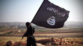 Islamic State militant carrying an IS flag, walking across a rocky landscape