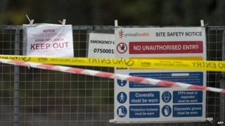 Signs are pictured attached to a gate at the entrance to a duck breeding farm where a case of bird flu has been identified in Nafferton, in Yorkshire