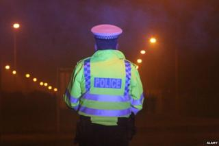 Police officer in dark with back turned