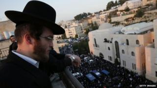 An ultra-Orthodox Jew looks down from a roof at people mourning near the bodies of the victims of an attack by two Palestinians on worshippers at a synagogue in Jerusalem
