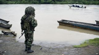 A Colombian soldier stands guard in the banks of the Atrato river in Las Mercedes, rural area of Quibdo, Department of Choco, Colombia, on November 19, 2014, where Colombian General Ruben Alzate was kidnapped
