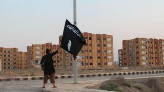 Islamic State fighter waves flag at the base of Division 17 in Raqqa province, Syria