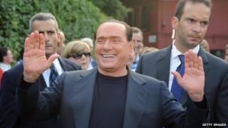 Silvio Berlusconi waves at a public appearance