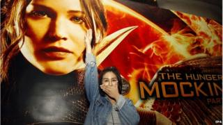 Thai pro-democracy activist Nacha Kong-udom closes her mouth and flashes a three-finger salute in front of a poster of The Hunger Games movie at a cinema in Bangkok, Thailand, 20 November 2014