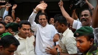 Maithripala Sirisena (C) waves to supporters in Colombo shortly after defecting from the ruling party and declaring himself as the common opposition candidate to challenge President Mahinda Rajapaksa (21 November 2014)