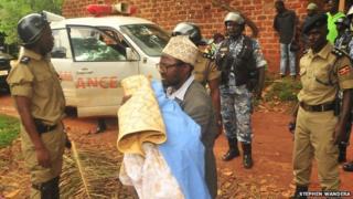 Man holding the body of Ryan Ssemaganda